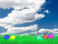 Easter eggs on a meadow lying with the sky and clouds in the background Royalty Free Stock Photography