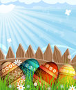 Easter eggs near a wooden fence in the meadow colorful painted with abstract pattern Royalty Free Stock Images