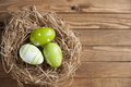 Easter eggs in a nest hay on wooden board Stock Photo