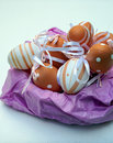 Easter eggs orange on a pink nest surrounded by white background its an image vertically Royalty Free Stock Image