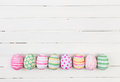 Easter eggs painted in pastel colors on a white wood background Stock Photography