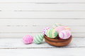 Easter eggs painted in pastel colors on white wood wooden background Stock Photos