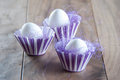 Easter eggs in purple and white cups with purple straw on wood Royalty Free Stock Photography