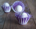 Easter eggs in purple and white cups with purple straw on wooden background Stock Photos