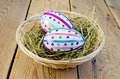 Easter eggs with ribbons and sequins in a basket two decorated multicolored braid sparkles the hay wicker on wooden boards Stock Photography