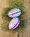 Easter eggs with ribbons and sequins on board two decorated multicolored braid sparkles as asterisks in the hay the background of Royalty Free Stock Images