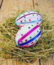 Easter eggs with ribbons and sequins in the hay two decorated multicolored braid sparkles as asterisks on background of wooden Stock Photo