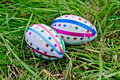 Easter eggs with ribbons and stars on grass two decorated multicolored braid sparkles as asterisks the green Stock Photos