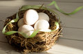 Easter eggs in rural basket with green ribbon. Chicken eggs in a nest close-up. Royalty Free Stock Photo