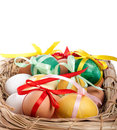 Easter eggs in a straw basket on the white Stock Photos
