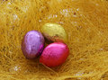 Easter eggs three colorful shiny chocolate eggs over straw Royalty Free Stock Photo