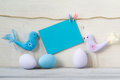 Easter eggs and two birds in pastel colors with a blank blue card on a white wooden background colored Stock Photos