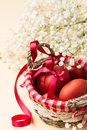 Easter eggs in the whitish nest and white flowers on beige table Royalty Free Stock Image