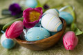 Easter eggs in a wooden bowl, carnations and tulip Royalty Free Stock Photos