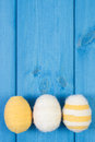 Easter eggs wrapped woolen string on blue wooden boards, copy space for text, decoration for Easter