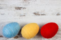 Easter eggs wrapped woolen string on wooden background, copy space for text, decoration for Easter