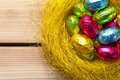 Easter eggs yellow nest wooden background holiday composition top view Royalty Free Stock Image