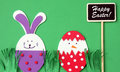 Easter hand made greeting card: festive plastic foam bunny and egg with blackboard isolated on green background