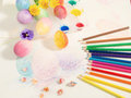 Easter hand-painted eggs with colored pencils,watercolors and spring flowers,arranged on colored drawing. Royalty Free Stock Photo