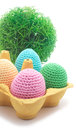 Easter handmade eggs with grass four in paper container on the ground isolated on white background crochet Stock Photos
