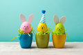 Easter holiday concept with cute handmade eggs, bunny, chicks and party hats in cup Royalty Free Stock Photo