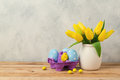 Easter holiday concept with tulip flowers and eggs on wooden table Royalty Free Stock Photo