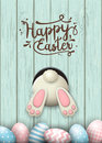 Easter motive, bunny bottom and easter eggs in fresh grass on blue wooden background, illustration
