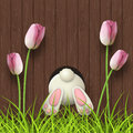 Easter motive, bunny bottom, pink tulips and fresh grass on dark brown wooden background, illustration