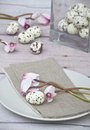 Easter quail eggs with pink cyklamen white speckled a plate a napkin glass bottle white feathers Royalty Free Stock Images