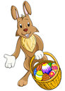 Easter rabbit gives basket with eggs Royalty Free Stock Photography