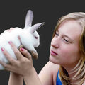 Easter rabbit in hands of the young girl holds a white small Stock Image
