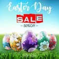 Easter sale banner with ornamental easter eggs in the grass