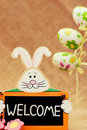 Easter smiling bunny with sign welcome and three painted eggs Royalty Free Stock Photography