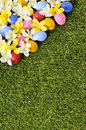 Easter eggs and flowers spring border background, green grass copy space, vertical