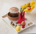 Easter still life with traditional kulich and by the bouquet of yellow red tulips daffodils next to quail eggs on a white Royalty Free Stock Photos
