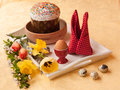 Easter still life with traditional kulich on white tray and by the bouquet of yellow and red tulips and daffodils next to quail Royalty Free Stock Image