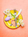 Easter table place setting with daffodils flowers cutlery plate eggs and empty label card on pastel pink background top view Stock Photography