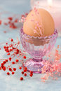 Easter table setting, decoration,egg in crystal cup with tender spring red and pink flowers, burning candle Royalty Free Stock Photo