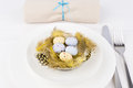 Easter table setting for a festive dinner a decorative yellow nest with colourful ester eggs on a plate Royalty Free Stock Images