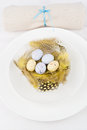 Easter table setting for a festive dinner a decorative yellow nest with colourful ester eggs on a plate Stock Photo