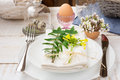 Easter table setting, white plates, cutlery, napkin, flowers in eggshell, green twigs, crystal cup, basket Royalty Free Stock Photo