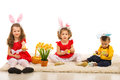 Easter three kids with bunny ears happy and eggs sitting on carpet home Stock Images