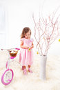 Easter tree preschool girl in pink dress decorating Stock Images