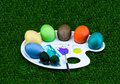 Easter white palette with multi-colored eggs coloring paint brush on green background Royalty Free Stock Photo