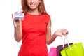 Easy shopping cheerful young woman in red dress holding bags and credit card while standing isolated on white Royalty Free Stock Image