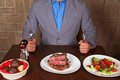 Eat a beef steak man holding knife and fork ready to Stock Photos