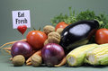 Eat fresh message sign with fresh raw vegetarian food including eggplant onion corn tomatoes walnut nuts and carrots against a Royalty Free Stock Photo