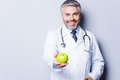 Eat healthy cheerful mature doctor in giving a green apple to you and smiling while standing against grey background Stock Photo