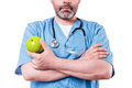Eat healthy close up of surgeon in blue uniform holding green apple while standing isolated on white Royalty Free Stock Photo