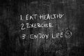 Eat healthy and exercise written on blackboard texture Royalty Free Stock Images